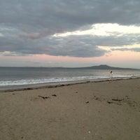 Photo taken at Mairangi Bay Beach by Marty K. on 3/26/2013